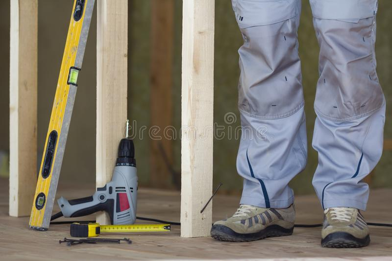 Close-up of worker`s legs and professional building tools at wooden frame for future wall in attic insulated unfinished room with royalty free stock photography