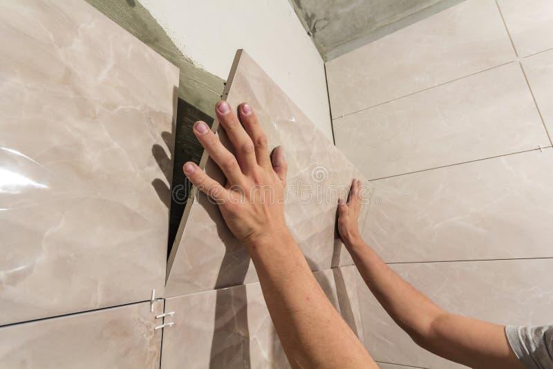 Close-up of worker tiler hands installing light beige ceramic tiles on walls of future bathroom. Tiles installation, home stock images