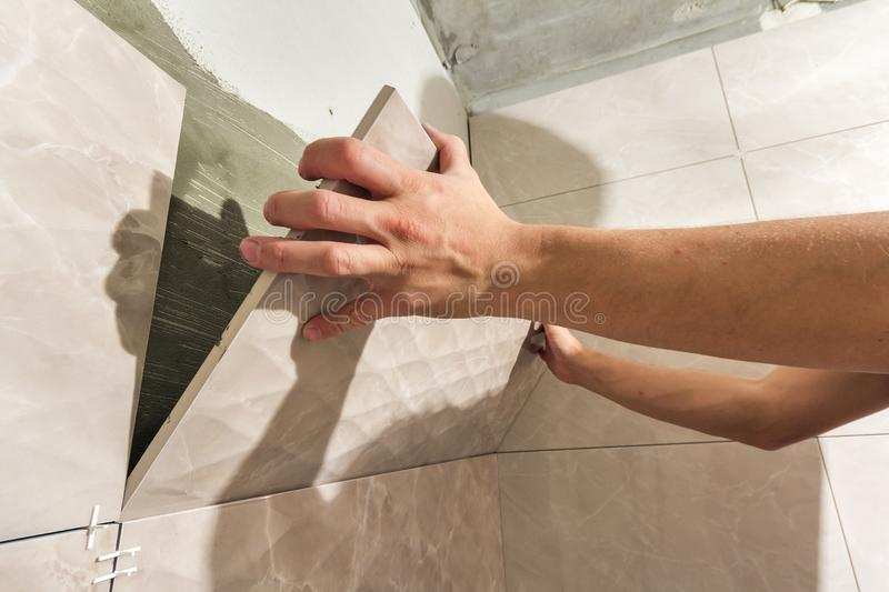 Close-up of worker tiler hands installing light beige ceramic tiles on walls of future bathroom. Tiles installation, home royalty free stock photo