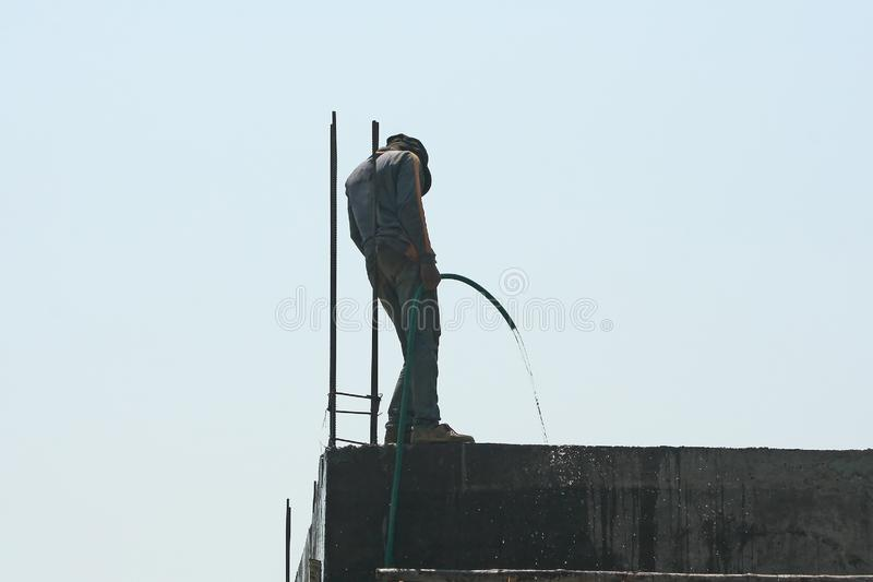 Worker using hose watering for cleaning the building stock photos