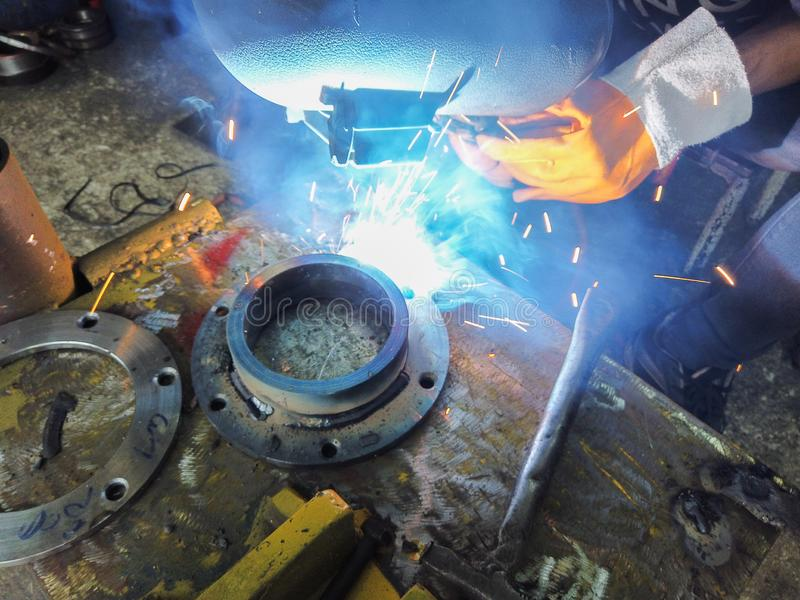 Close up worker welding steel with smoke and colourful of lights in industrial work shop stock image