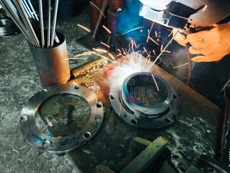 Close up worker welding steel with smoke and colourful of lights in industrial work shop stock photography