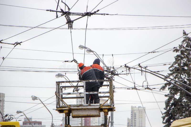 Workers on the tower repair the contact mains network for trolley buses royalty free stock image