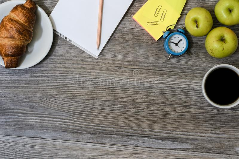 Close up of workplace: cup of coffee, apples, plate with croissant, notepad and pencil, alarm clock an a table royalty free stock images