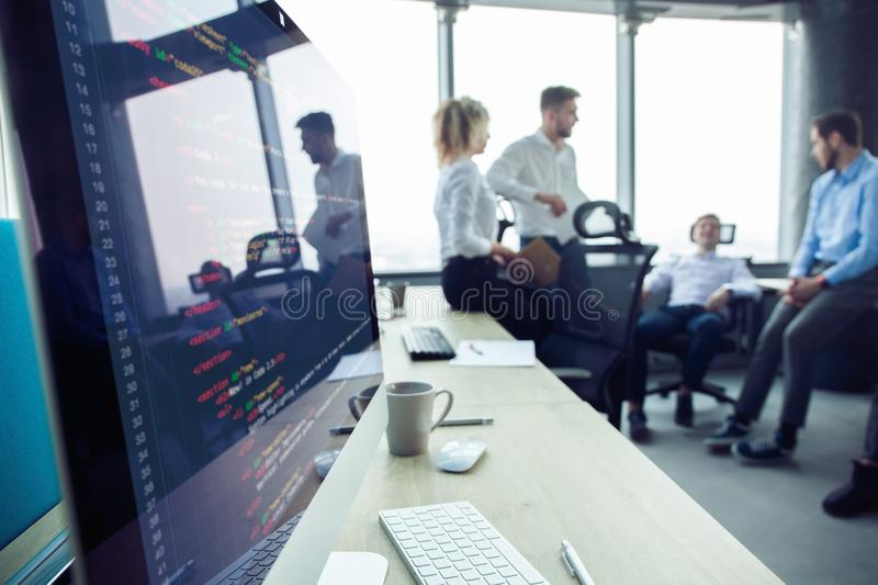 Close-up of workplace in modern office with business people behind. Colleagues meeting to discuss their future financial royalty free stock images
