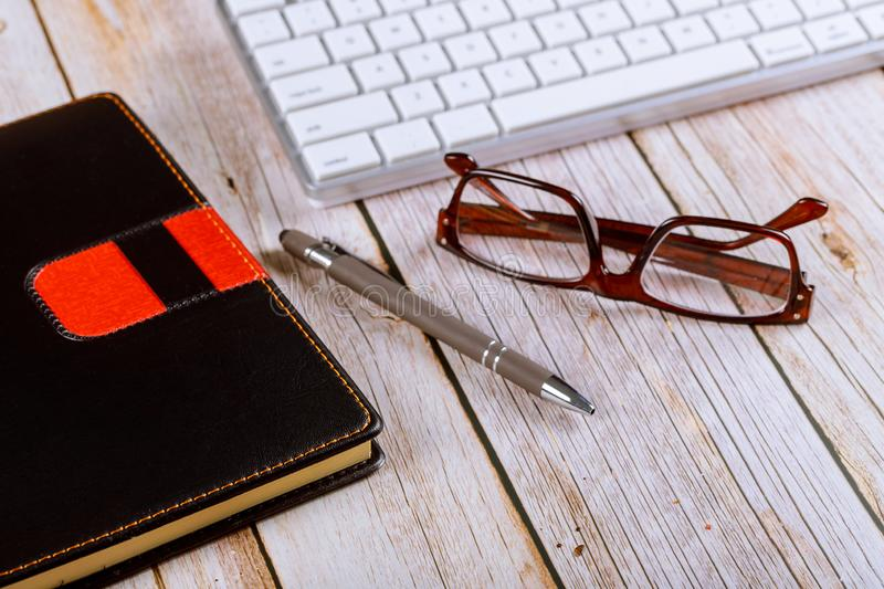 Close up workplace office desk table, reading eye glasses on wooden table with other office stuffs keyboard, notebook and pen royalty free stock photo