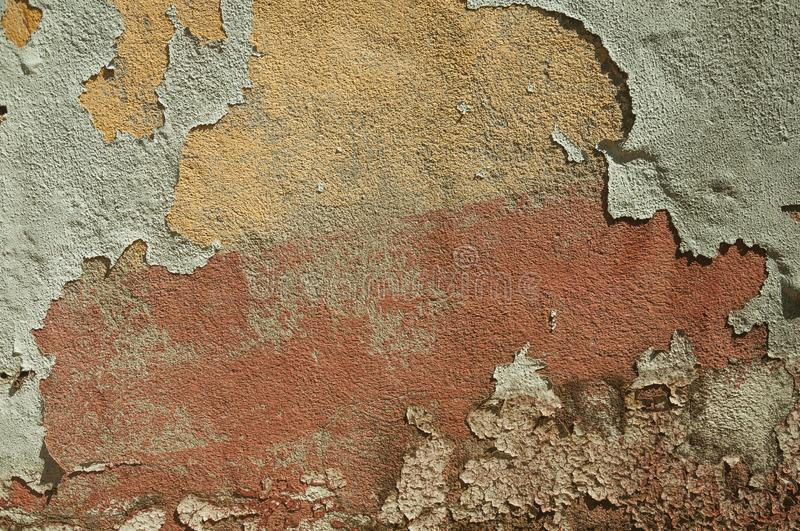 Worn wall with plaster covered by peeled paint. Close-up of worn wall with rough plaster covered by peeled paint, forming a singular background at Belmonte. A royalty free stock photography