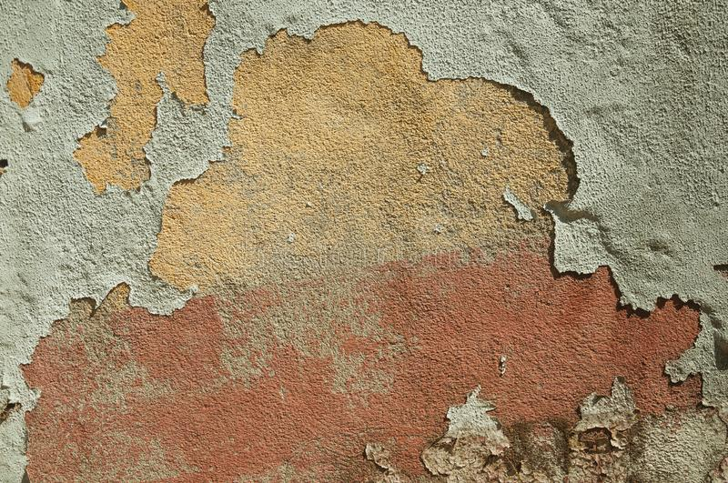 Worn wall with plaster covered by peeled paint. Close-up of worn wall with rough plaster covered by peeled paint, forming a singular background at Belmonte. A royalty free stock image
