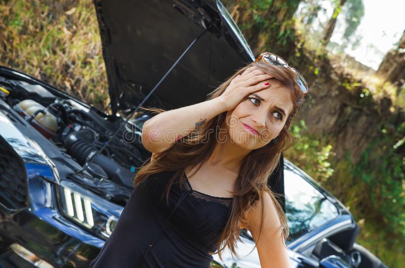 Close up of worried woman wearing sunglases in her head, black t-shirt and jeans, having a problem with black car on a stock images