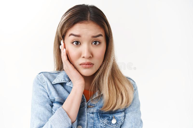 Close-up worried young asian female blonde hearing disturbing awful story stare full disbelief empathy nervously listen. Close-up worried young asian female stock photography
