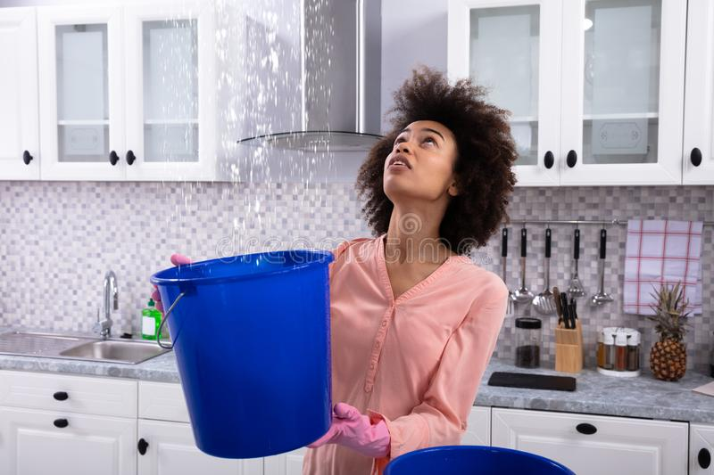 Woman Collecting Water Leaking From Ceiling In Bucket royalty free stock photos