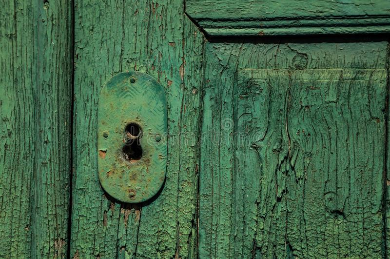 Close-up of wrought iron keyhole in an old wooden worn door royalty free stock photos