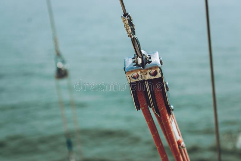 Close up of yacht equipment. Part of yacht with red ropes and capstan. Sailing boat pulley with nautical rope. Marine background stock photography