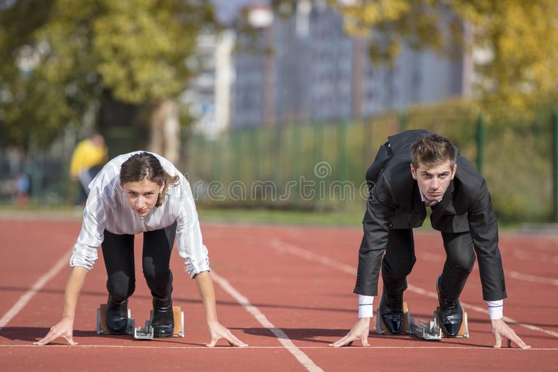 Close up of 20 year old businessmen and businesswoman ready to run at start point. stock photo
