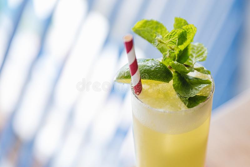 Close-up Yellow Cocktail with soda bubble topping with mint leaves and slice of lime with red and with strip straw stock photography
