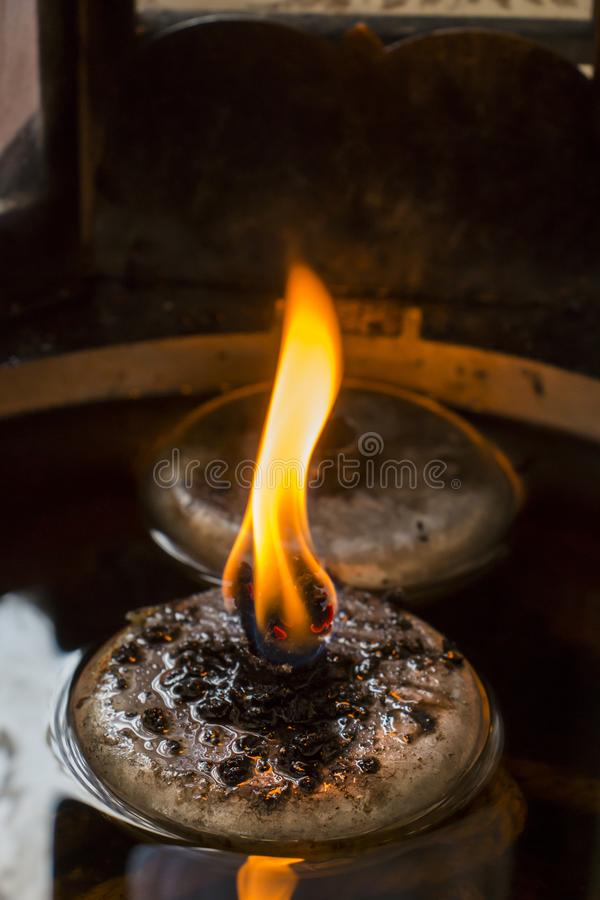 Close up of fire burning in old oil lamp. stock photo
