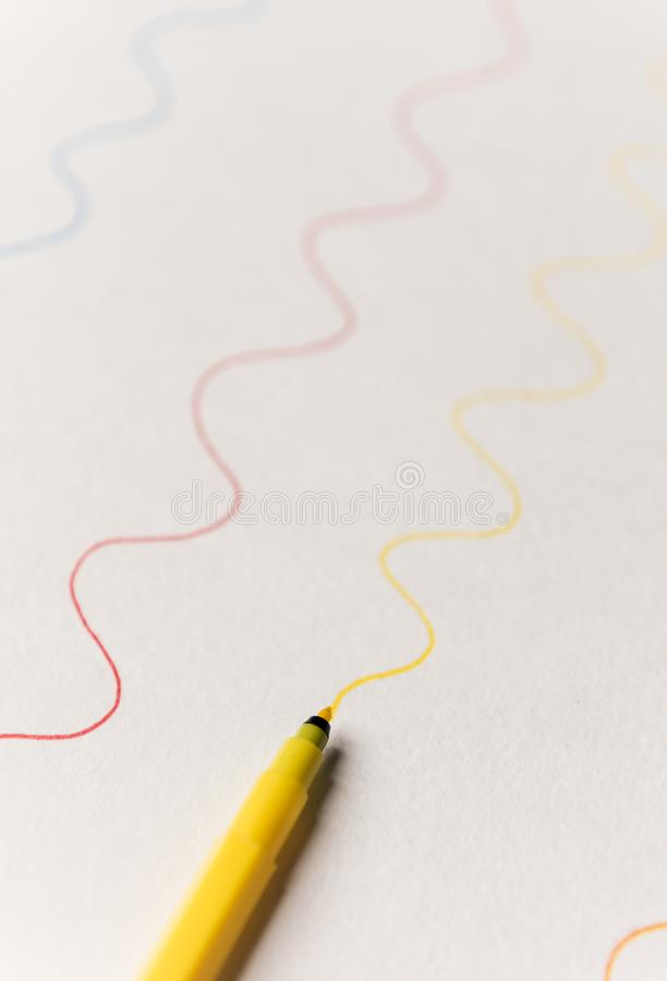 Close up of yellow highlighter painting line on white paper. Close up of yellow highlighter painting wavy line on white paper. Lines for logo, text royalty free stock photography