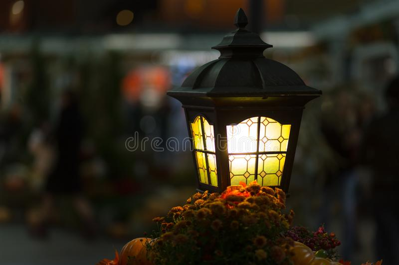 Close-up yellow lantern glows yellow. street lighting. Creating cozy romance bright lamp with copyspace. On blurred background stock photo