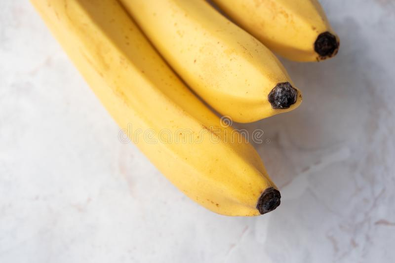 Close-up yellow ripe fresh banana on marble kitchen table with selective focus. Concept healthy eating diet. Fruit for dessert. Top view royalty free stock photography