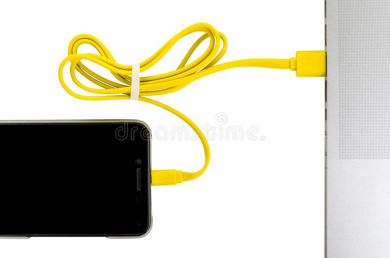 Close-up yellow usb cable connect phone and laptop computer new technology concept. Horizontal frame stock image