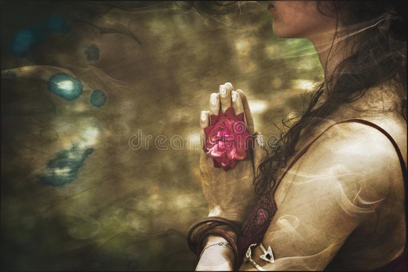 Close up of yoga woman hands in namaste gesture with rose flower. Vintage look royalty free stock image