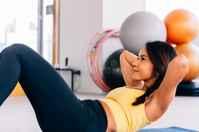 Close-up of young active and fitness Asian woman doing sit ups and crunches inside gym with exercise ball in background.  royalty free stock photos