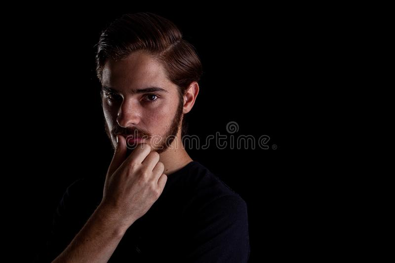 Young adult male looking sinister or contemplative. Color expressive dramatic effect, dark and moody series. Close up of young adult male looking sinister or stock images