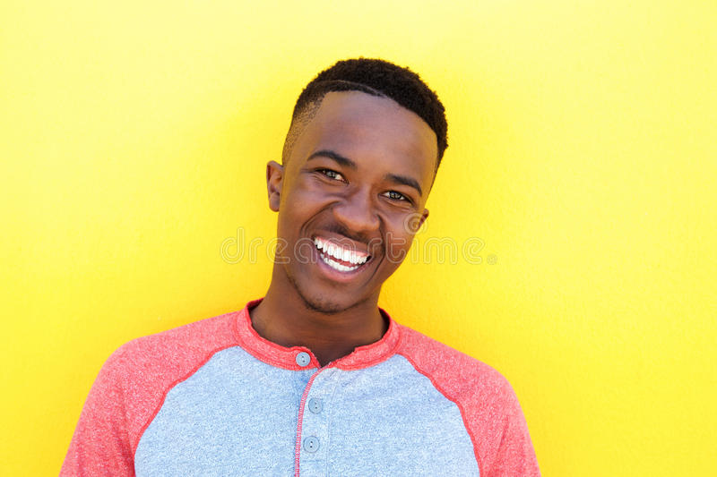 Close up young african ameircan man smiling against yellow background royalty free stock images