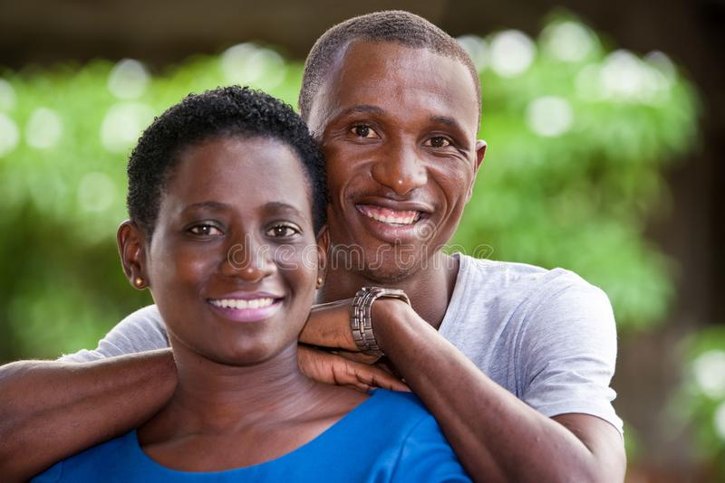 Close up of young african couple, happy. Young african couple standing up looking at camera laughing royalty free stock photo