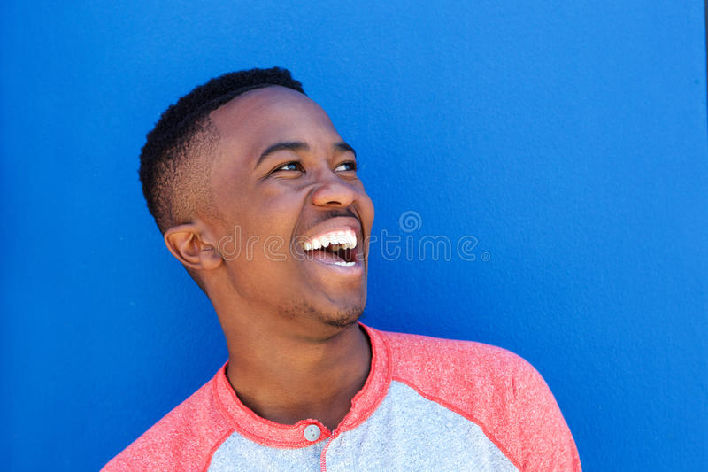 Close up young african man laughing against blue background stock image