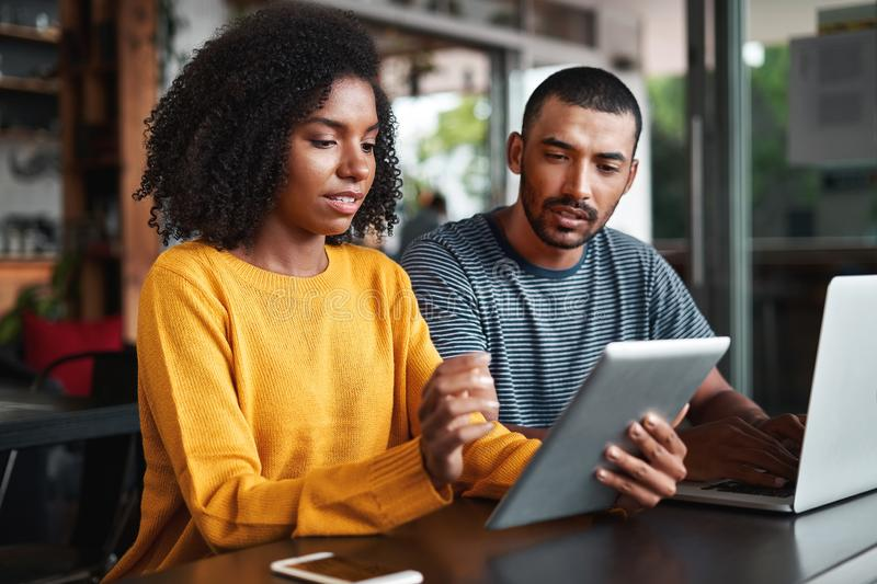 Young couple looking at digital tablet in cafe royalty free stock images