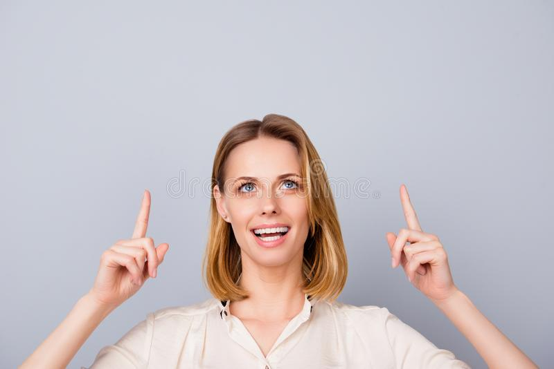Close up of young amazed blond woman in a beige shirt, standing royalty free stock images