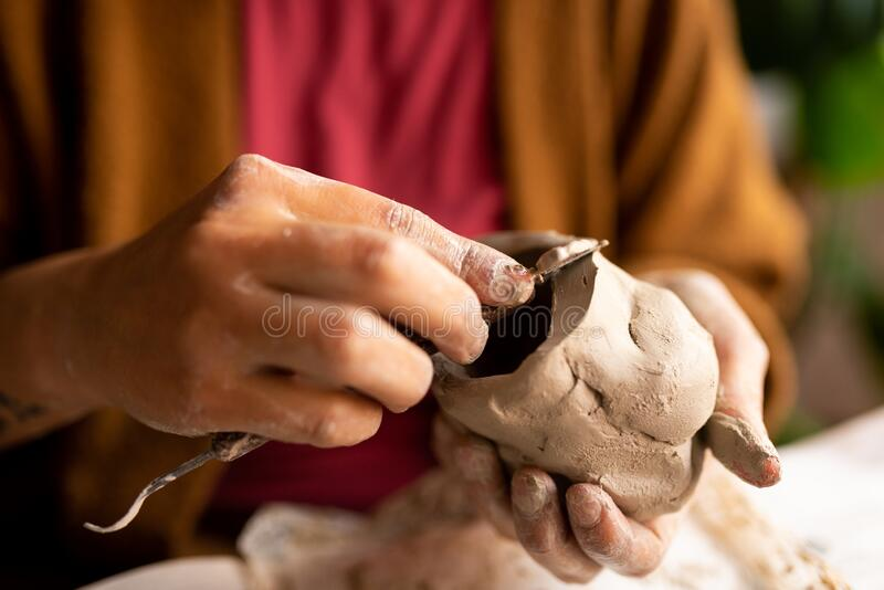 Close up of young artisan woman working with clay with tools, a manual work that requires craftsmanship and skills, also a hobby. Close up of young artisan woman stock photo
