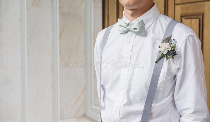 Close-up young Asian man in white shirt with bow tie and suspender royalty free stock photography
