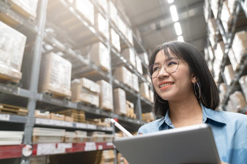 Close up of young attractive asian woman, auditor or trainee staff work stocktaking inventory in warehouse store by computer royalty free stock photos