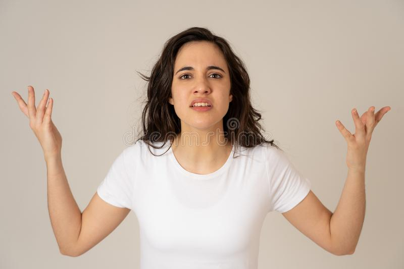 Portrait of beautiful young latin woman with angry and furious face. Human expressions and emotions. Close up of young attractive frustrated latin woman in royalty free stock photography
