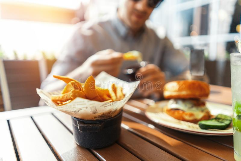 Close up of young attractive man eating french fries and burger at street cafe. Close up of young attractive smiling man with tattoo eating french fries and stock images