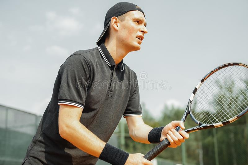 Close up of young attractive man playing tennis at tennis court. stock photos