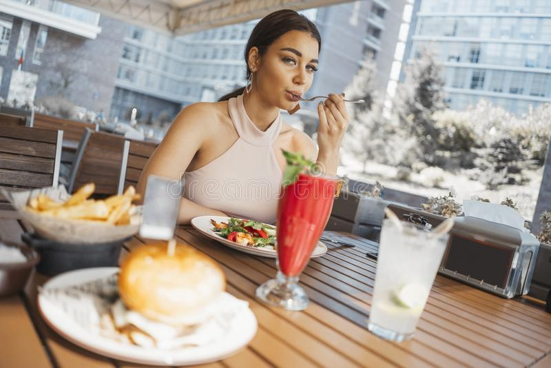 Close up of young attractive woman eating salad at street cafe. royalty free stock image