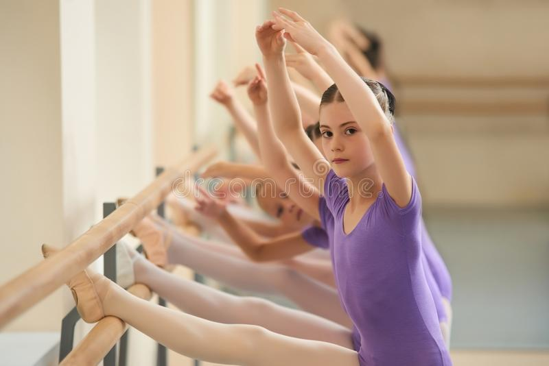 Close up young ballerina with her legs on barre. royalty free stock image
