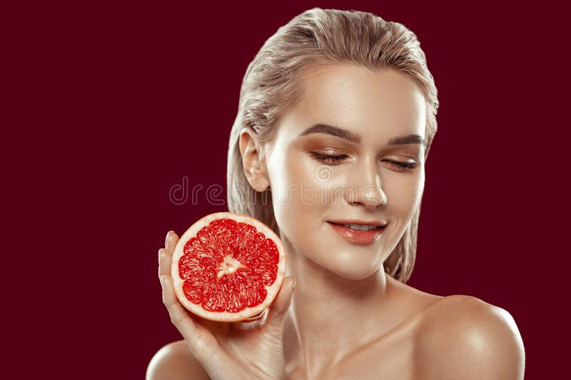 Close up of young beaming model posing with grapefruit royalty free stock photography
