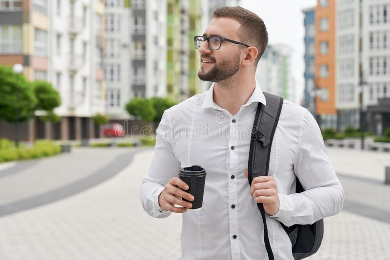 Positive student standing with backpack and coffee cup. royalty free stock photography