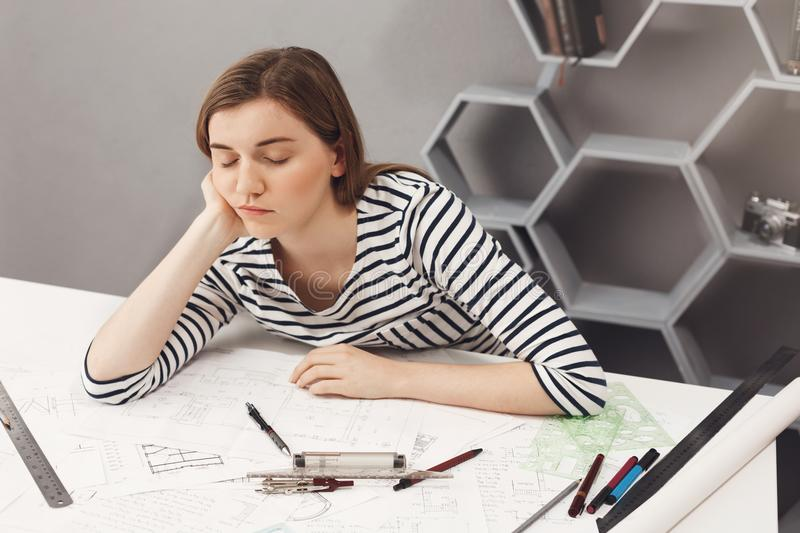 Close up of young beautiful sleepy freelance architect girl holding head with hand, falling asleep while preparing royalty free stock photo