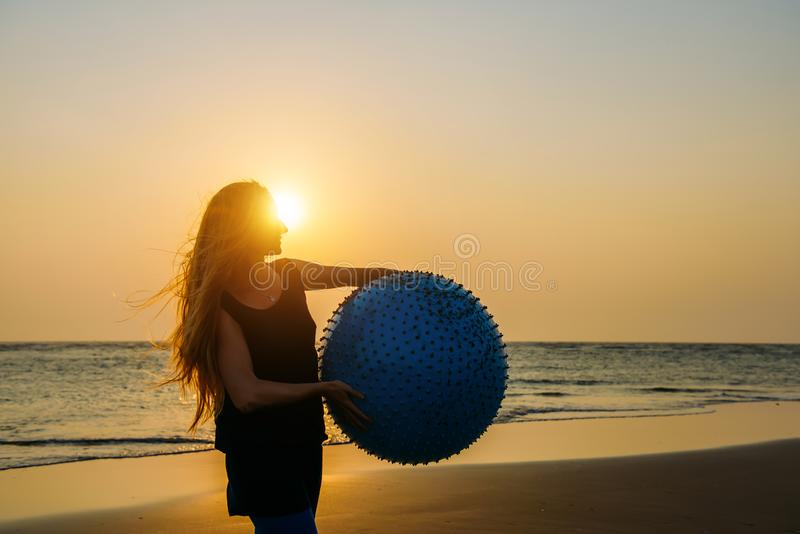 Close-up of young beautiful woman with long blonde hair holds big fitness ball standing on beach in the light of setting sun. Silhouette of slender girl with stock image