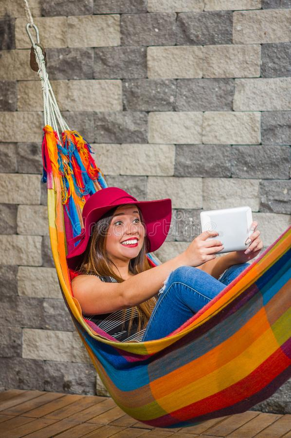 Close up of young beautiful woman wearing a red fashion hat and relaxing in a hammock and taking a selfie with her. Tablet, in blurred background royalty free stock photos
