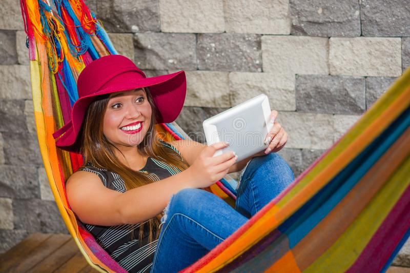 Close up of young beautiful woman wearing a red fashion hat and relaxing in a hammock and taking a selfie with her. Tablet, in blurred background stock photography