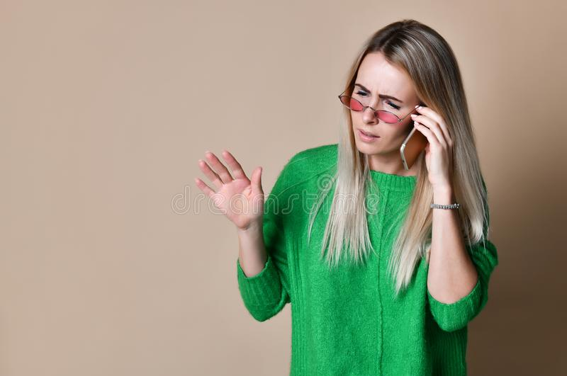 Close up Young blonde Woman Talking to Someone on her Mobile Phone While Looking Into the Distance with Happy Facial Expression stock photo