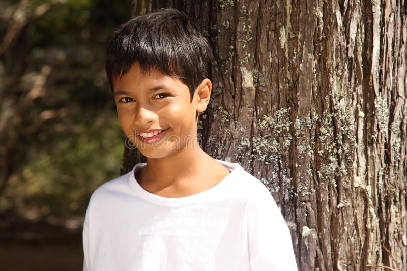Close up young boy big smile leaning against tree stock photo