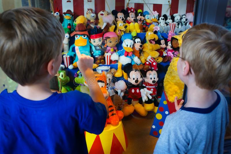 Children Child Selecting Disney Toy. Close up of young boys picking out souvenir toy at window display of colorful Disney soft toy collection royalty free stock photo