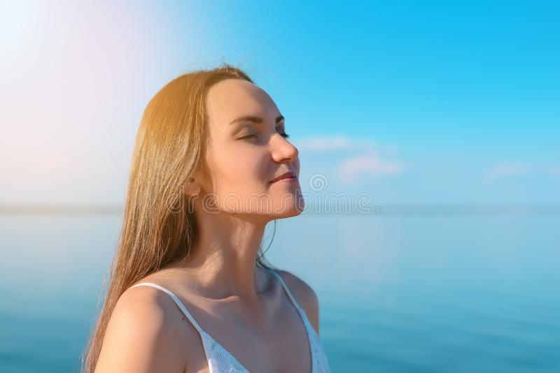 Close - up of a young brunette breathes clean sea air on the background of clear sky and sea, fresh air, freedom, ecology stock image